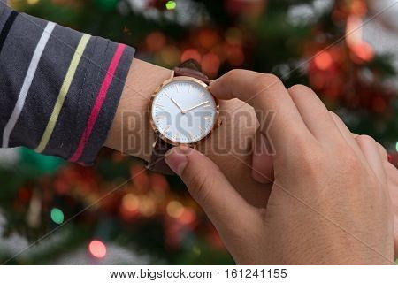 Wrist watch on girl's hand in christmas time in front of a Christmas tree in background