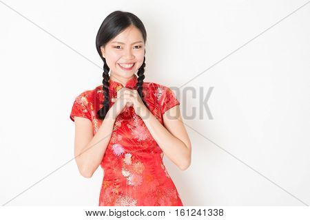 Portrait of young Asian girl in traditional qipao dress smiling and greeting, celebrating Chinese Lunar New Year or spring festival, standing on plain background.