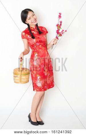 Young Asian woman in traditional cheongsam dress holding gift basket and plum blossom smiling, celebrating Chinese Lunar New Year or spring festival, full length standing on plain background.
