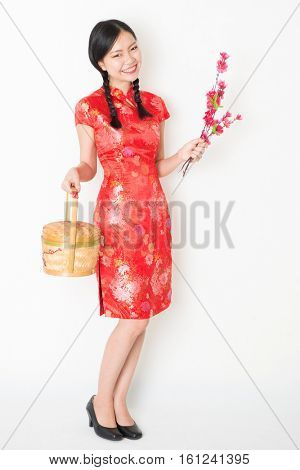 Young Asian woman in traditional cheongsam dress holding gift basket and plum blossom smiling, celebrating Chinese Lunar New Year or spring festival, full body standing on plain background.