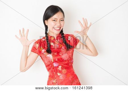 Portrait of young Asian girl in traditional qipao dress with surprised face expression, celebrating Chinese Lunar New Year or spring festival, standing on plain background.