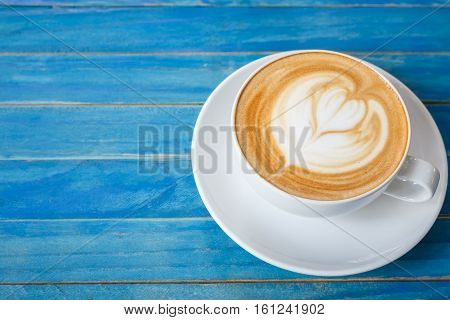 Top View Hot Latte Coffee In White Cup On Blue Vintage Wooden Table