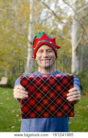 Smiling man holding a Christmas present in front of him.