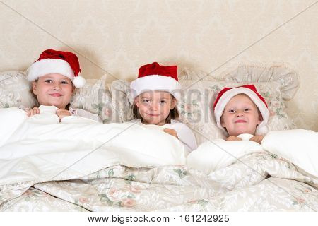 Funny little girls with santa hats in bed