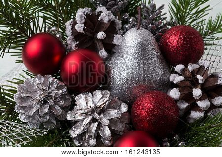 Christmas red ornaments silver pine cones and glitter pear. Christmas decoration with fir branches and red baubles. Christmas table centerpiece.