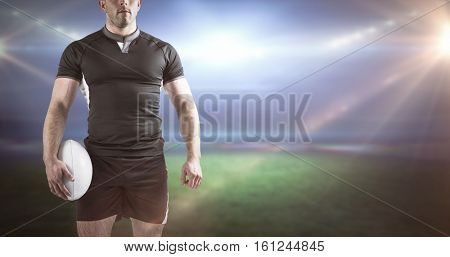 3D Tough rugby player holding ball against rugby stadium