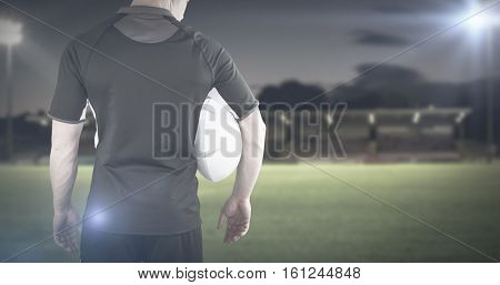 3D Rugby player holding a rugby ball against pitch