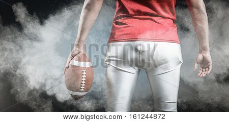 3D Mid section of sportsman with American football against digitally generated image of color powder