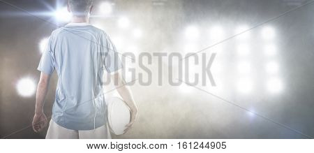 3D Rugby player holding a rugby ball against splashing of yellow color powder