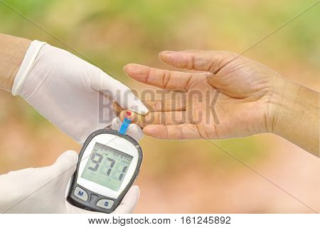 Hand of doctor checking for blood glucose meter, the blood sugar value is measured on a finger and pink bokeh background.