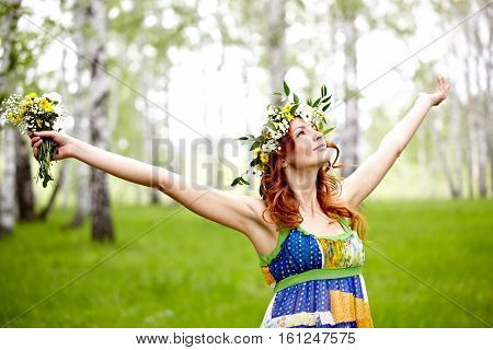 Beautiful woman in flower crown enjoying nature, her arms outstretched