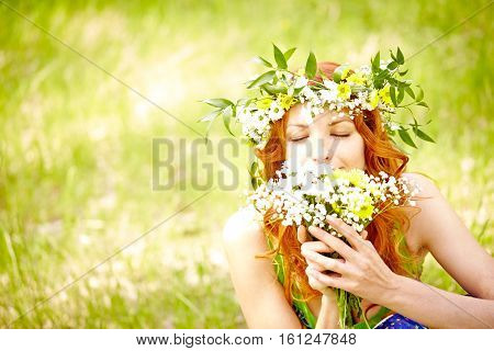 Summer woman smelling fresh wildflower bouquet in nature