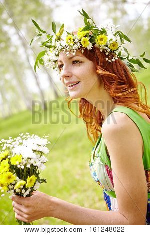 Red-haired woman in wildflower crown admiring non-urban view
