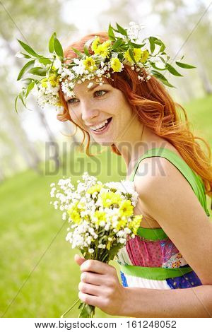 Outdoor portrait of cheerful red-haired woman in flower crown holding wildflower bouquet