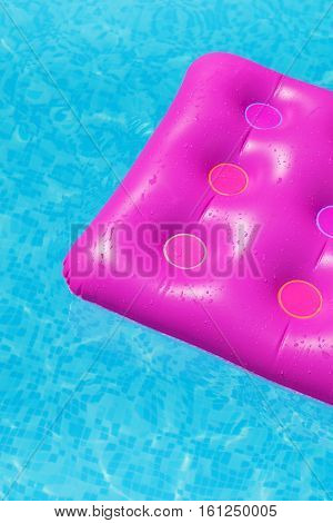 Pink air mattress on a swimming pool - holiday tropical background concept
