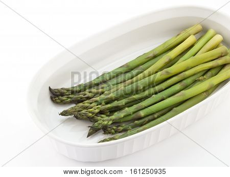 Steamed green asparagus spears on white serving plate