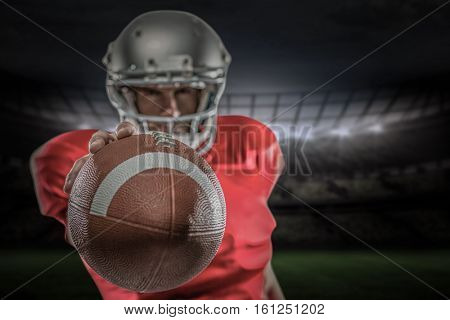 3D American football player in red jersey holding ball against rugby stadium