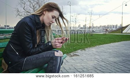 Dissapointed girl with long blonde hair in leather jacket straightens hair use gadget sitting on the bench in the wind, telephoto