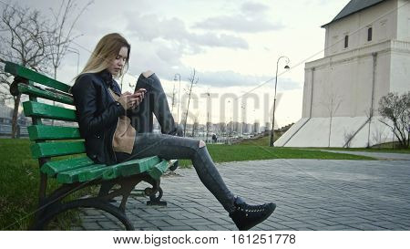 Cute happy girl with long blonde hair in leather jacket straightens hair use gadget sitting on the bench, horizontal