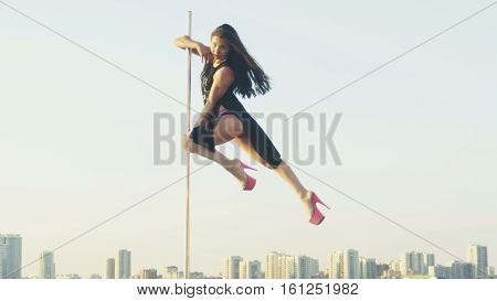 Fit attractive girl dancing on the portable pole at summer day over the skyline, slow-motion, near river, telephoto