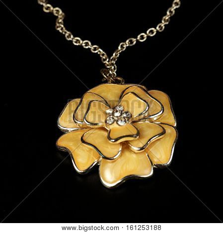 Yellow pendent in the form of a flower costume jewelry close up on a black background.
