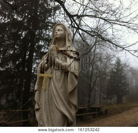 small white Madonna statue in the woods