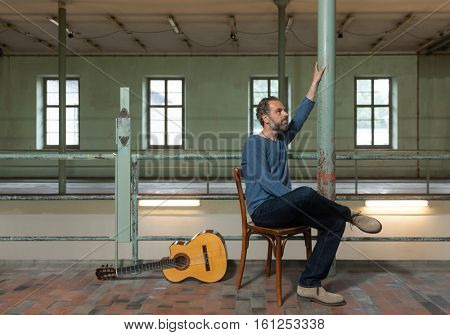 Musician sitting on a wooden chair with his guitar on the floor