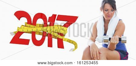 3D Young woman sitting and exercising with dumbbell against digitally generated image of new year with tape measure