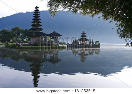 Pura Ulun Danu water temple framed by bamboo on lake brataan near bedugal bali indonesia