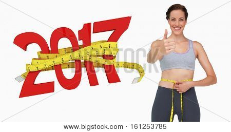 3D Fit woman measuring waist while gesturing thumbs up against new year with tape measure