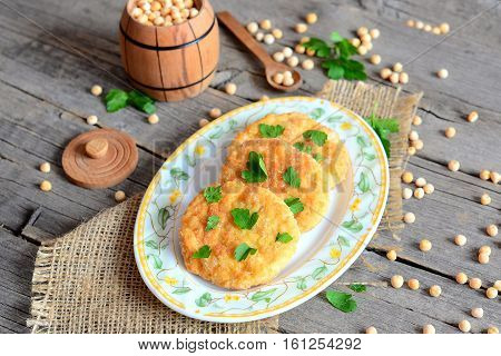 Vegetarian high protein burgers. Healthy cutlets cooked from dried peas and decorated with parsley leaves. Small spoon, decorative barrel with dried peas on a wooden table. Vegetarian food concept