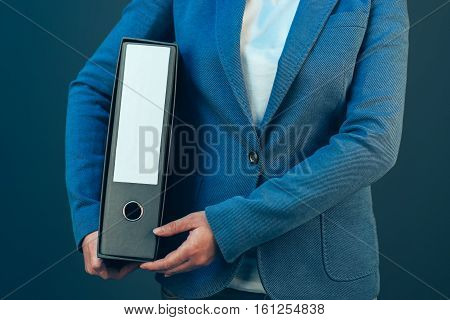 Business company accountant holding document binder with archived paperwork and other corporate legal sheets
