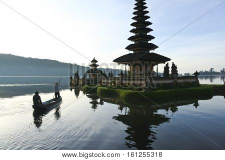 People on boat approcahing Pura Ulun Danu water temple on lake brataan near bedugal bali indonesia