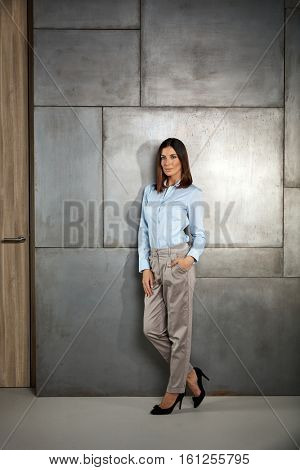Young businesswoman standing against wall, looking at camera. Full size.