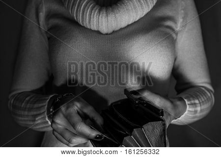 Woman holding empty wallet at night like stealing money - black and white