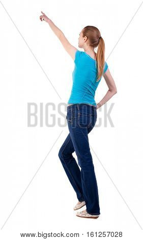 back view of walking  woman  in   jeans and shirt pointing. beautiful blonde girl in motion.  backside view of person. Isolated over white background. blonde teen while walking indicates that a top