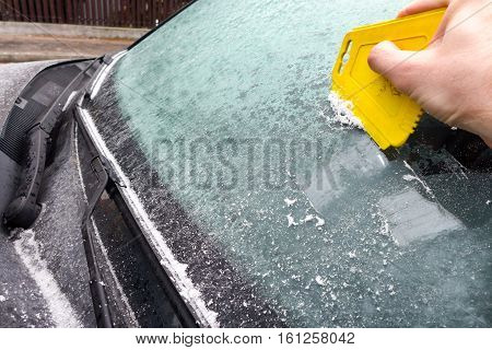 Scraping ice from the frozen car windscreen