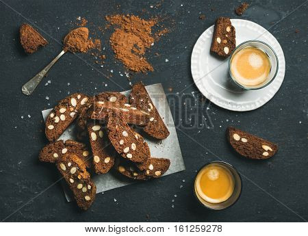 Dark chocolate and sea salt Biscotti with almonds and two glasses of coffee espresso over dark stone background, top view, selective focus, horizontal composition