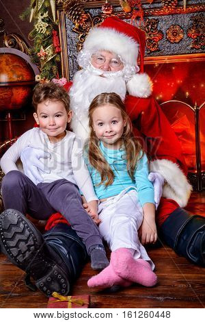 Good old Santa Claus and happy children celebrate Christmas with gifts. Beautiful room with Christmas tree and fireplace decorated for Christmas.