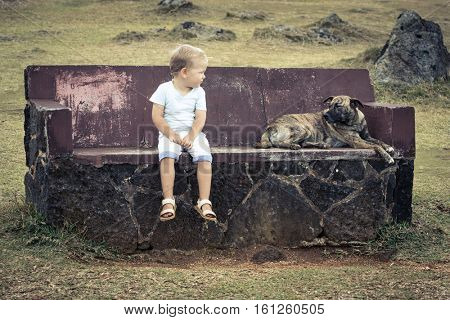 Child and dog are sitting on a bench