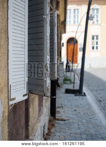 Selective focus on the window with white wooden shutters against the blurred background of another building of the street. White wooden shutters against the blurred background of the road.