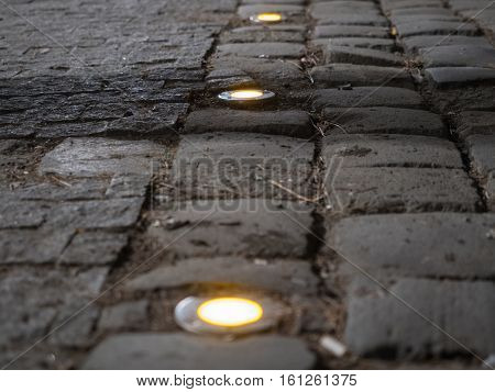 Picture of the cobblestone paved road with spotlight close up. Dark brown cobblestone road pattern close up. Selective focus on the middle of the picture. Spotlights against the blurred background.