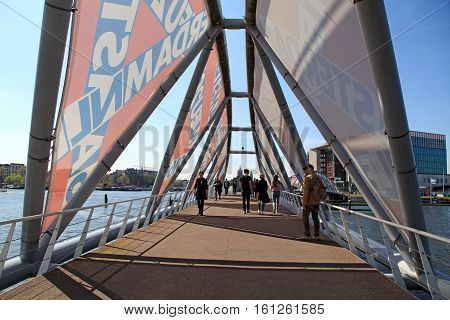 AMSTERDAM, NETHERLANDS - MAY 6, 2016: People walking on the modern bridge near the Nemo museum in Amsterdam, Netherlands