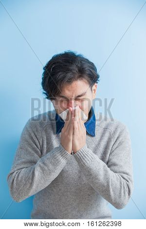 man is sick and sneezing with blue background asian