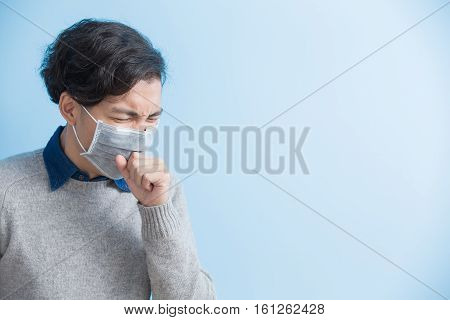 man is coughing isolated on blue background asian