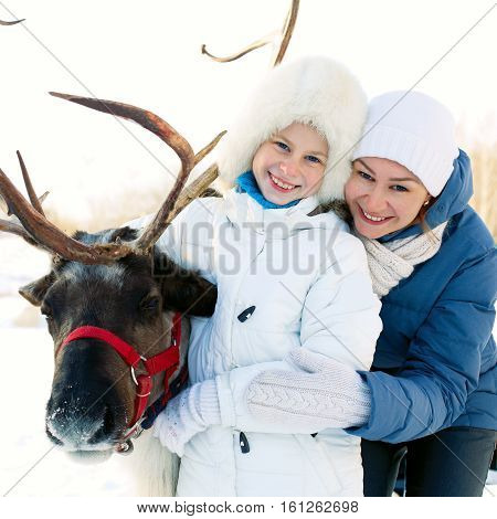 Happy little girl with mom hugging her reindeer. Winter playtime.
