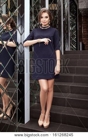 Beautiful Young Girl Model Costs In Dark Blue Dress On A Background Of A Wall Mirror, Makeup