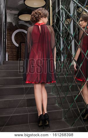 Beautiful Young Girl Model Is Back In A Red Dress On A Background Of A Wall Mirror, Makeup