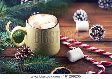 Close view at mug with hot chocolate, christmas tree, tangerines, peppermint stick and marshmallow on a wooden background. Dark photo. Empty space for text. Toned for art effect