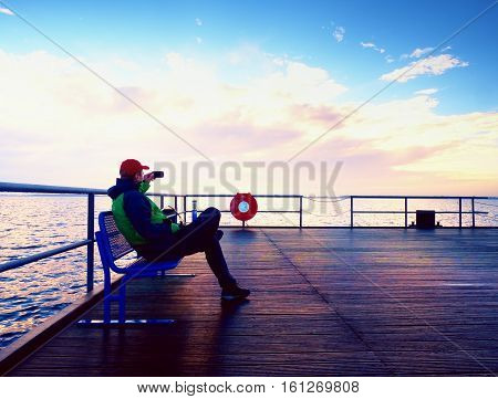 Tourist Sit On Bench On Mole And Take Pohotos. Man Enjoy Morning At Sea